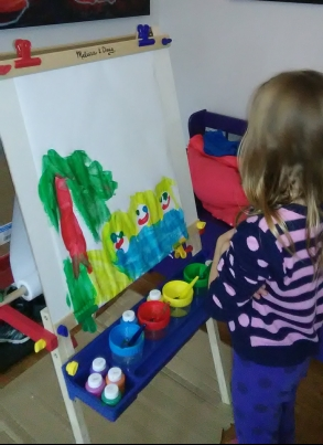 Violette using the easel to paint Mommy, Gigi and her